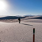 One hiker walking on white sand dunes