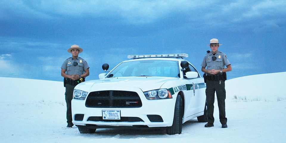 Two law enforcement rangers standing on each side of a patrol car surrounded by white sand dunes