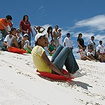 A group of youth sledding on white dunes