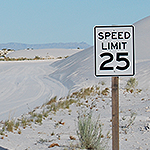 White 25 mph  speed limit sign along a sand road