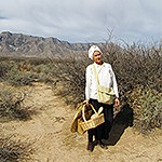 Woman dressed in historic apparel carrying a basket stands on dirt path with mountains in the background