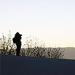 Photographer focuses camera silhouetted against a bright sky