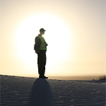 Silhouette of person on dune with sun setting in background.