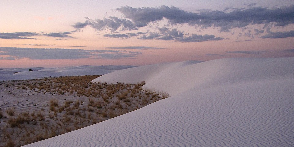 sunrise with  light pink and purple clouds in the sky and white sand dunes with ripples in the foreground