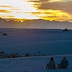 Visitors enjoying a sunset in the dunes.
