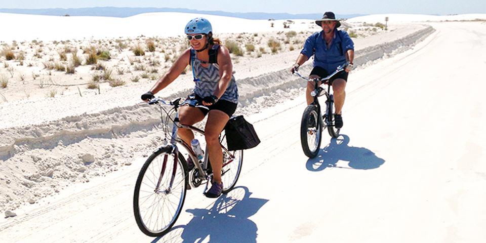 Visitors riding bicycles down dunes drive.