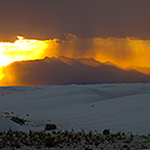 Sunset with rain showers and white dunes in the foreground