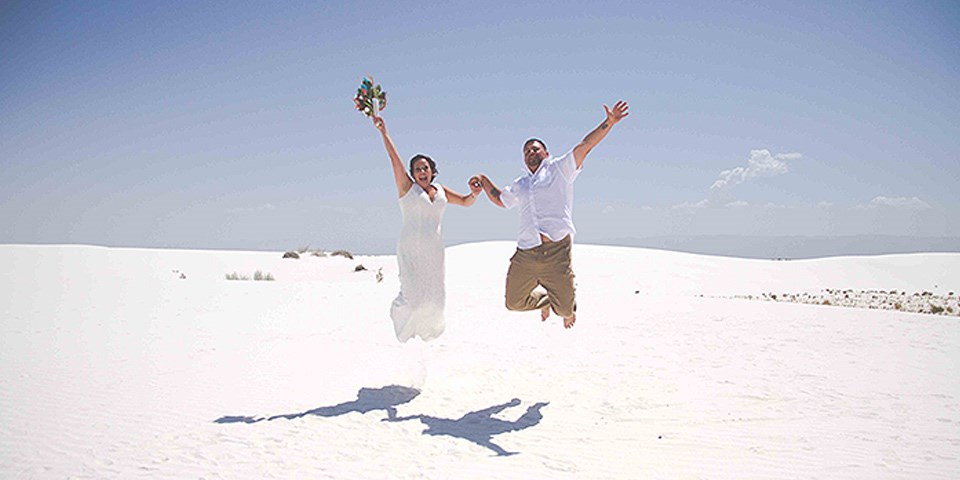 A bride and groom jumping into the air holding hands