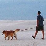 A man walking tan dog on leash in white sand