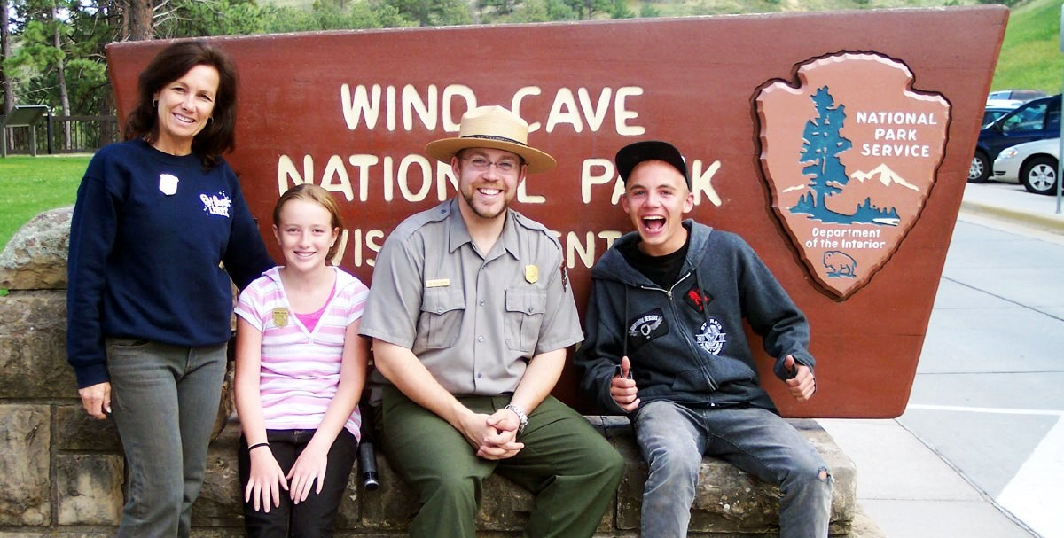 Junior rangers sitting with a park ranger in front of the Wind Cave National Park historic sign