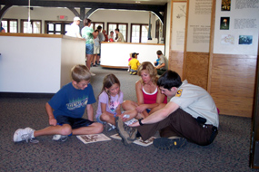 SCA Volunteer works with children to complete their Junior Ranger books