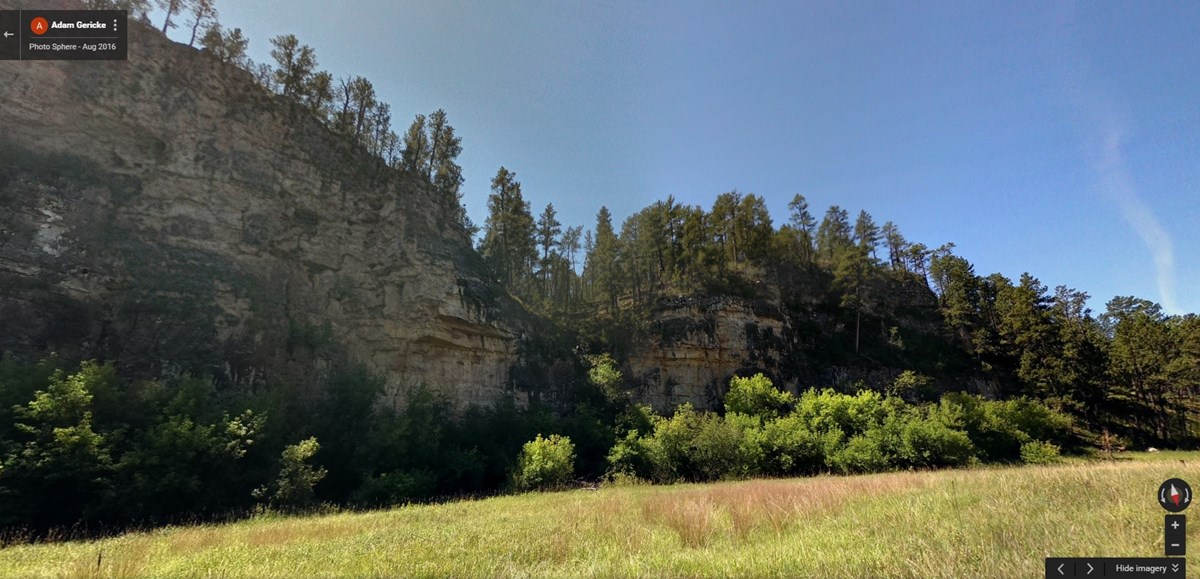 Rising limestone cliff above intermittent stream