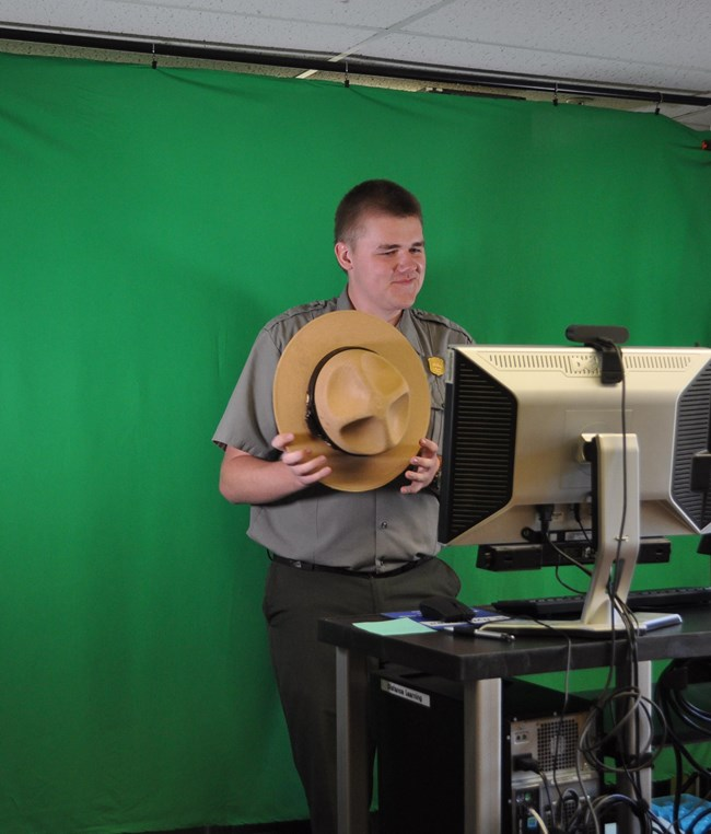Ranger holding their flat hat in a studio.