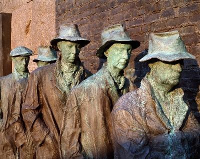 Statues of men in a line. They are wearing hats and tattered coats.