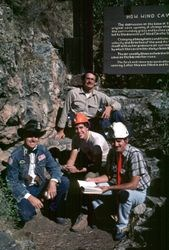 Four men of the 50-mile survey posing in front of the natural entrance to Wind Cave