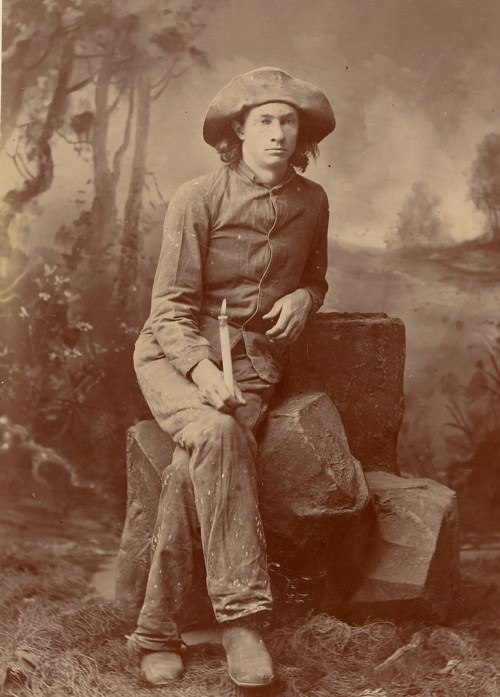a sepia photo of a young man with a wide brimmed hat sitting on a rock holding a candle