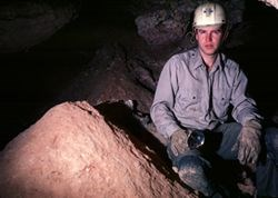 Warren Netherton inside Wind Cave wearing caver gear (helmet, gloves, headlamp)
