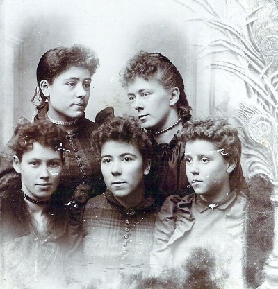five young women with curly hair and old fashioned dresses pose in a black and white photo
