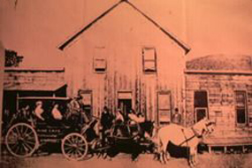 A tallyho stagecoach in front of the Wind Cave Hotel