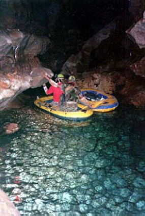 Two cavers using rafts to cross Transition Lake