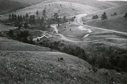 Historic black and white photograph of the visitor center area, including roads, prairie, and pine forest