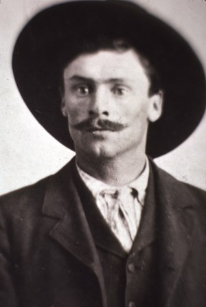black and white portrait of a young man with a mustache and a wide brimmed hat