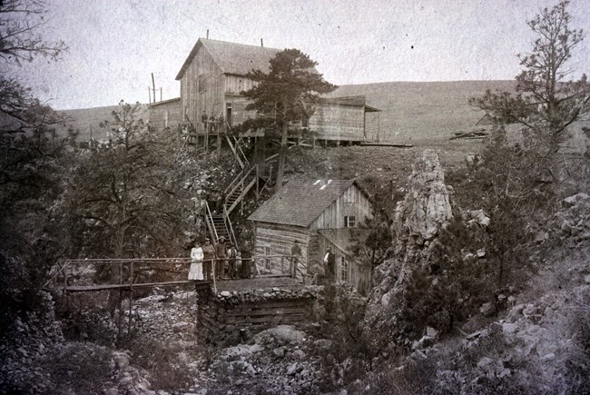 black and white photo of two old wooden buildings along a ravine, a small bridge crossing the ravine has a group of visitors in old clothing standing on it