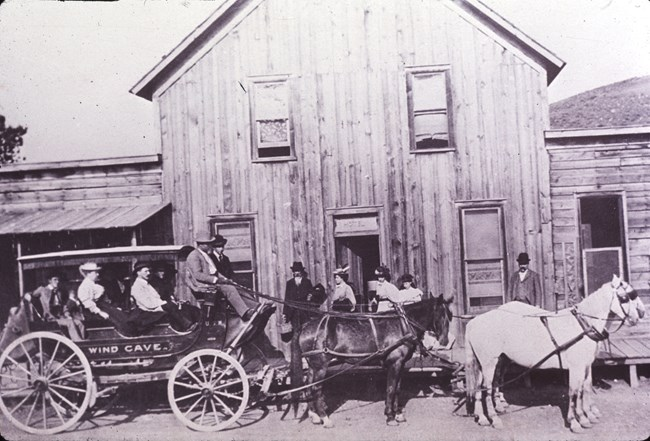 black and white photo of a stagecoach with Wind Cave written on it drawn by four horses in front of a wooden building