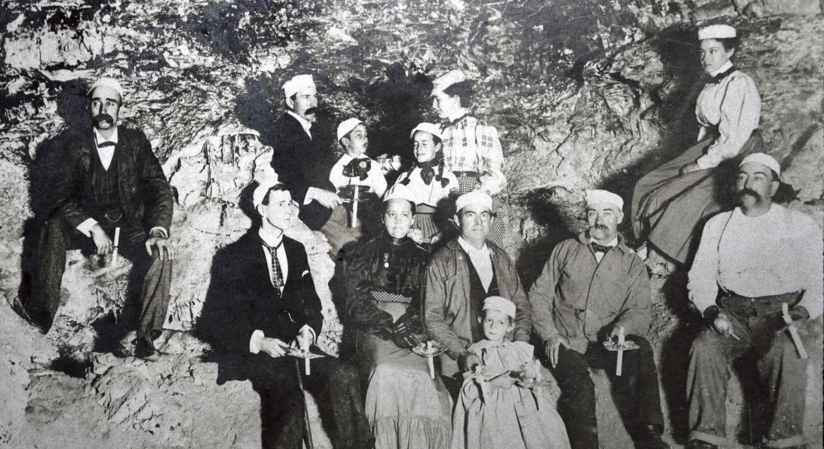 black and white photo of a small group of people in clothing from the 1890s holding candles wearing white caps in a cave room