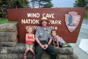 Two junior rangers sit beside a park ranger in front of the Wind Cave National Park historic sign