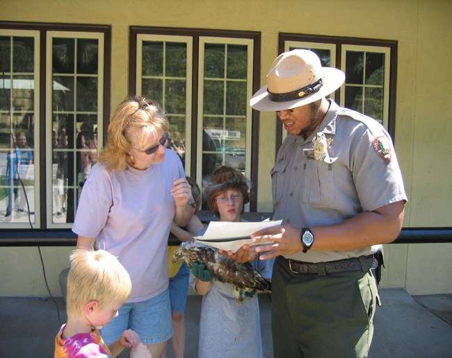 Park ranger giving directions to a family