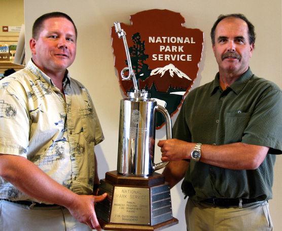 "Jim McMahill (left), Fire Management Officer at Wind Cave National Park, accepts  the ""drip torch"" trophy from Doug Alexander (right), Midwest Region Fire and Aviation Management Officer."