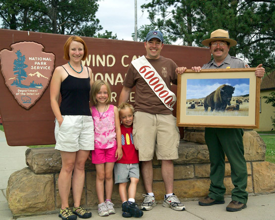 The Bree family from Wisconsin, Jeannette, Mallory, Aidan, and Joe, were presented a framed bison print by Acting Superintendent Steve Schrempp for being the cave's sixth-millionth visitors.