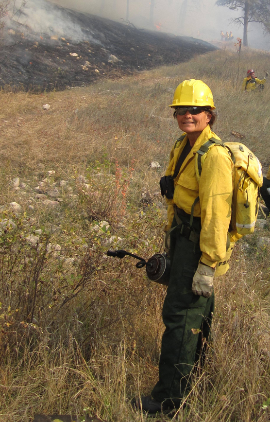 Beth Burkhart, dressed in yellow Nomex, standing near a fire line with a drip torch in her hand.