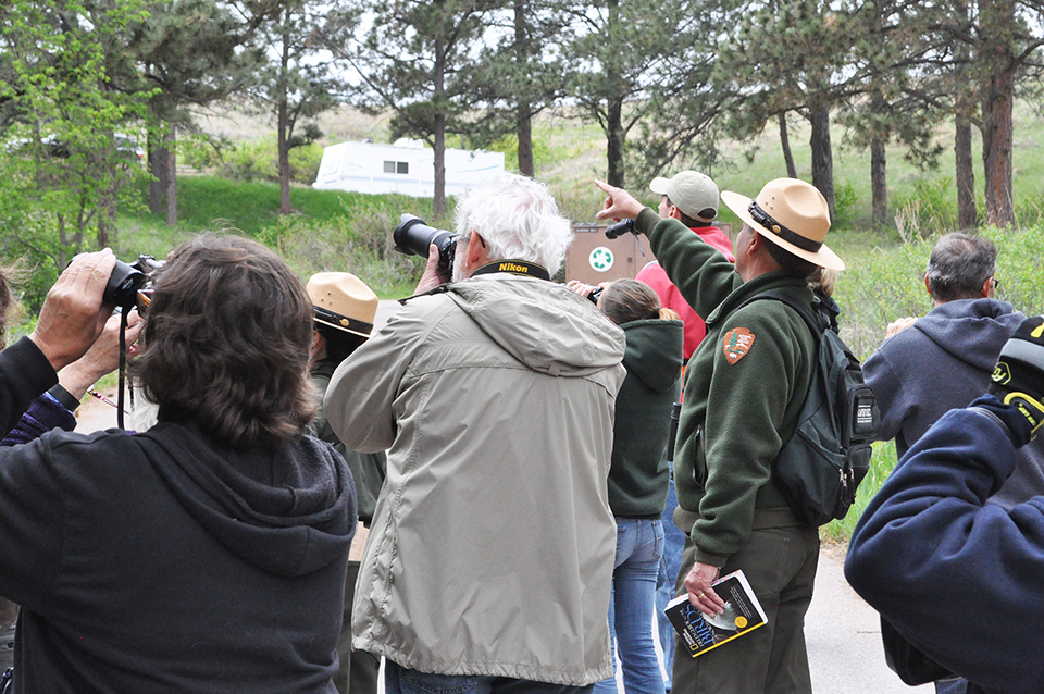 Group of people on a bird walk with a ranger pointing toward the left of the photo.