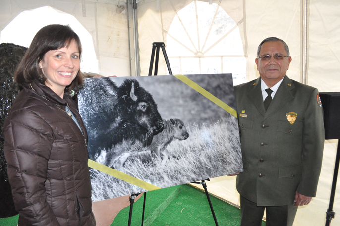 Kelly Keenan Aylward from the Wildlife Conservation Society standing next to a photo of bison. Standing to the right of the bison photo is Superintendent Vidal Dávila.