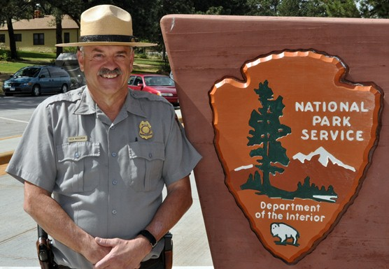 Chief Ranger Rick Mossman standing by Wind Cave National Park sign.