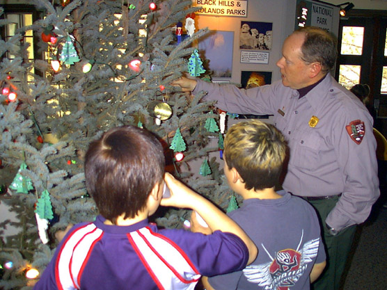 Ranger helping children decorate Christmas Tree