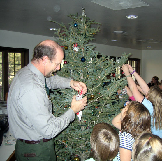 Park employee Dan Morford helping students decorate the visitor center tree.