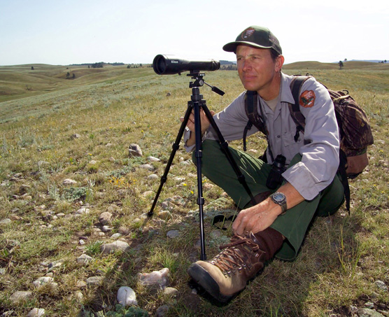 Biological Science Technician Duane Weber sitting behind a spotting scope on the prairie looking for elk.