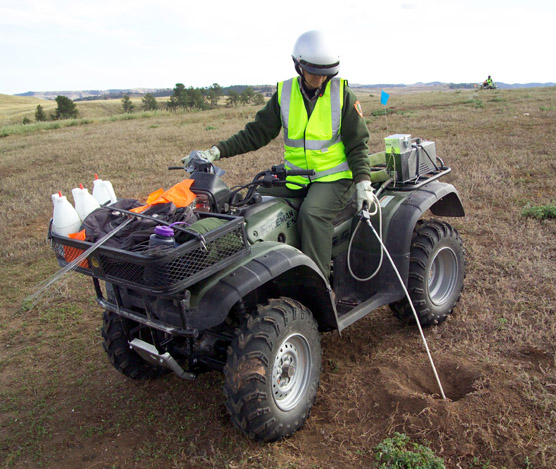 Biological technician Barb Muenchau sites on an ATV and uses a Techni-Duster to apply Deltamethrin into a prairie dog burrow.