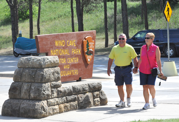 Couple holding hands walking by Wind Cave National Park Visitor Center sign.