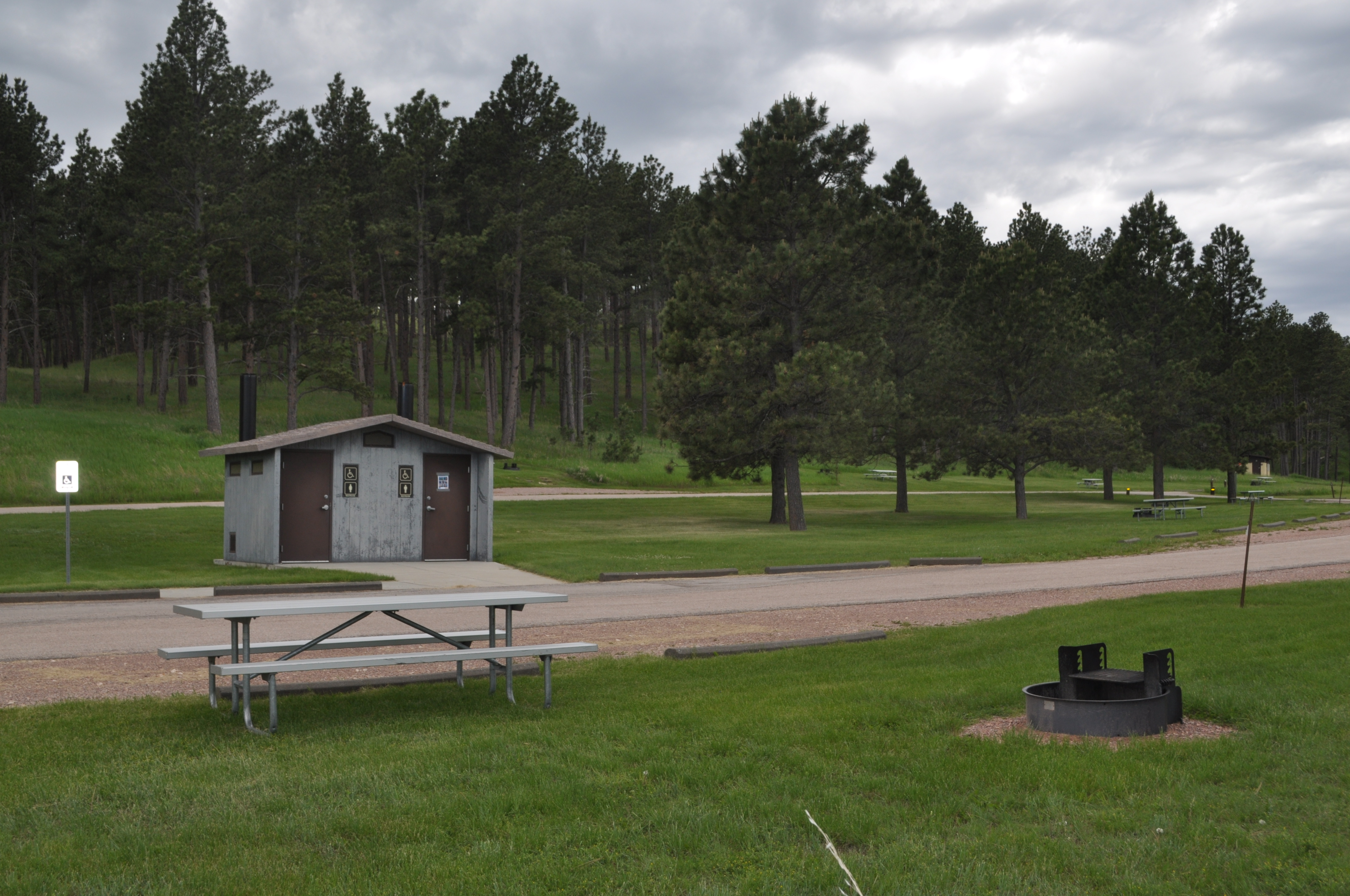Picnic table on green grass near a fire grate with a vault toilet nearby. There is a slight hill in the background covered with ponderosa pine trees.