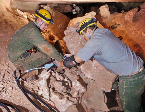 Two park employees installing new lights in Wind Cave