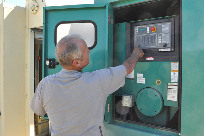 Maintenance specialist Jeff Simmons pointing to button on a backup generator.