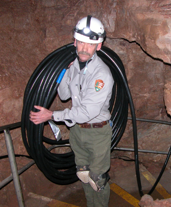 Maintenance Worker Mark Salmon carrying 135 feet of cable weighing 100 pounds for Wind Cave's new lighting system.