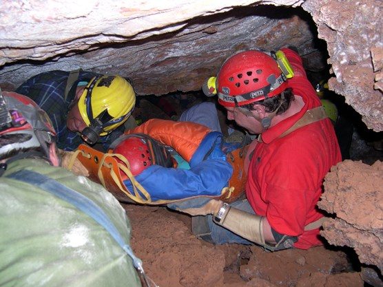 "Park employees practice carrying a ""patient"", seen here wrapped in a sleeping bag and carried on a plastic litter, from deep in Wind Cave."