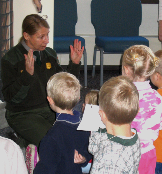 Ranger Mary Laycock kneeling in front of children while giving a program.