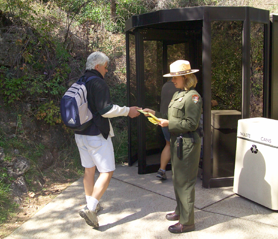 Female park ranger standing at Walk-In Entrance to Wind Cave accepting a ticket from a visitor.