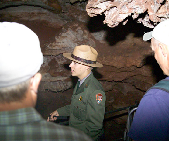 Uniformed male park ranger speaking with several visitors on a cave tour